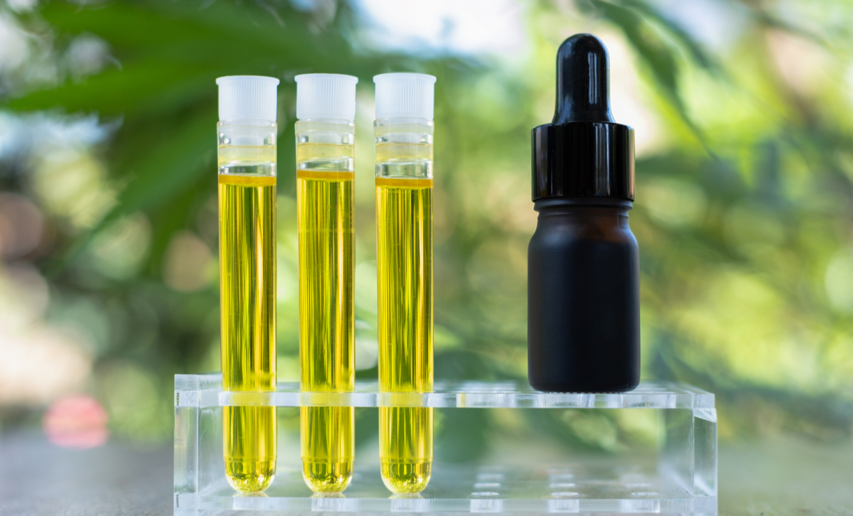 CBD oil in vials next to a dropper bottle.